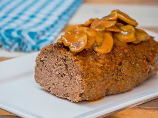 Meatloaf covered in a mushroom sauce on a serving dish.
