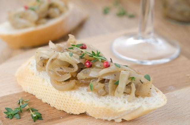 Crostini with onion and thyme on a serving board.