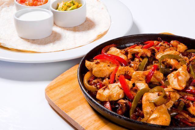 chicken and red pepper stir fry in a pan with dips in the background.