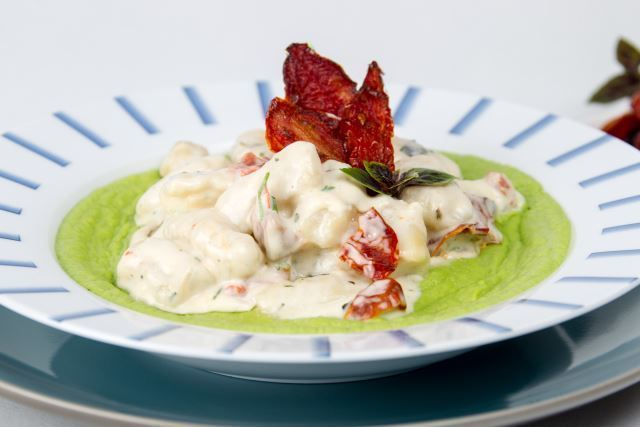 Creamy Gnocchi with Pea Puree and sun dried tomatoes on a plate.