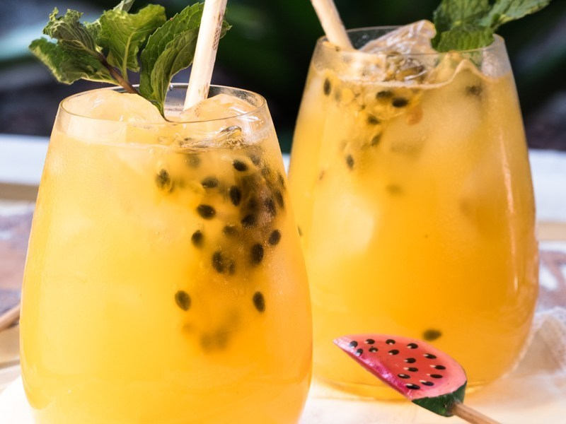 Passion Fruit and Ginger Mojitos in glasses with watermelon swizzle sticks.