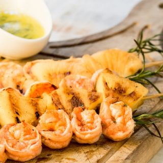 Shrimp On Rosemary Skewers with a serving sauce.