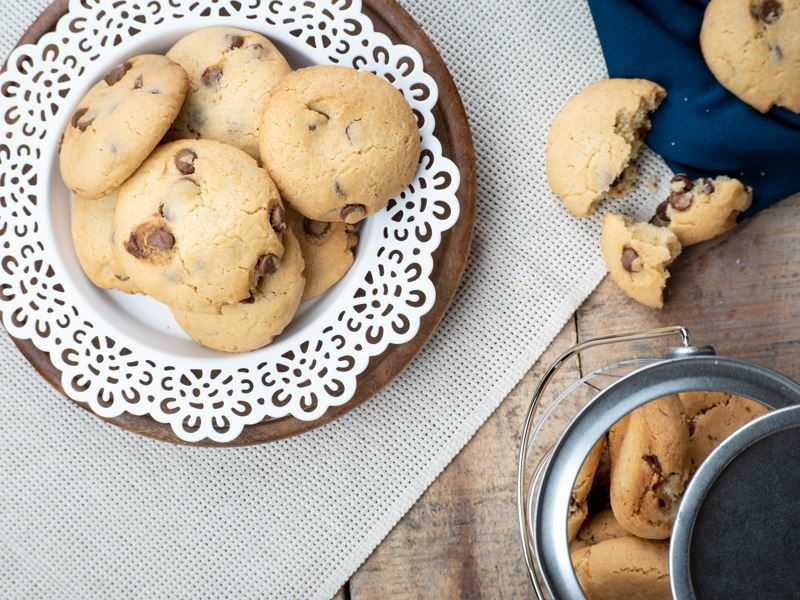 Chocolate Chunk Almond Cookies on a plate with paper doily.