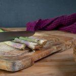 Chopping asparagus stems off.