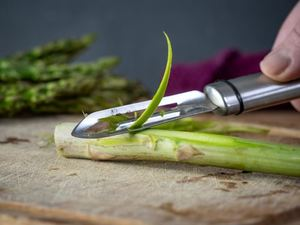 Peeling asparagus stems.