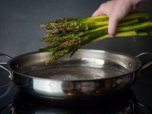 Adding asparagus stems to pan.