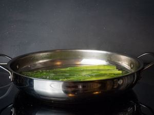 Cooking asparagus stems in a frying pan.