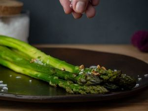 Seasoning cooked asparagus on a plate.