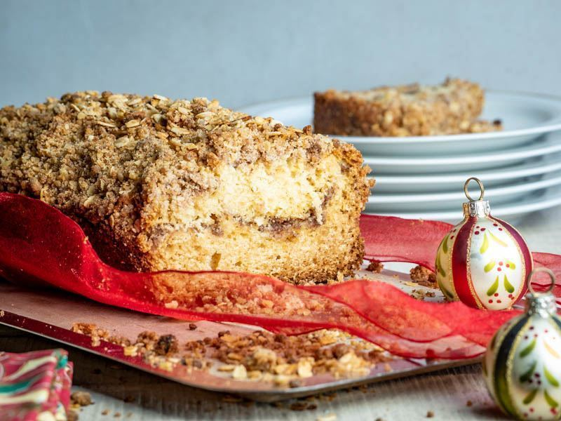 Coffee Cake with Cinnamon & Oats Crumble on a dish, with christmas decorations on wooden background.
