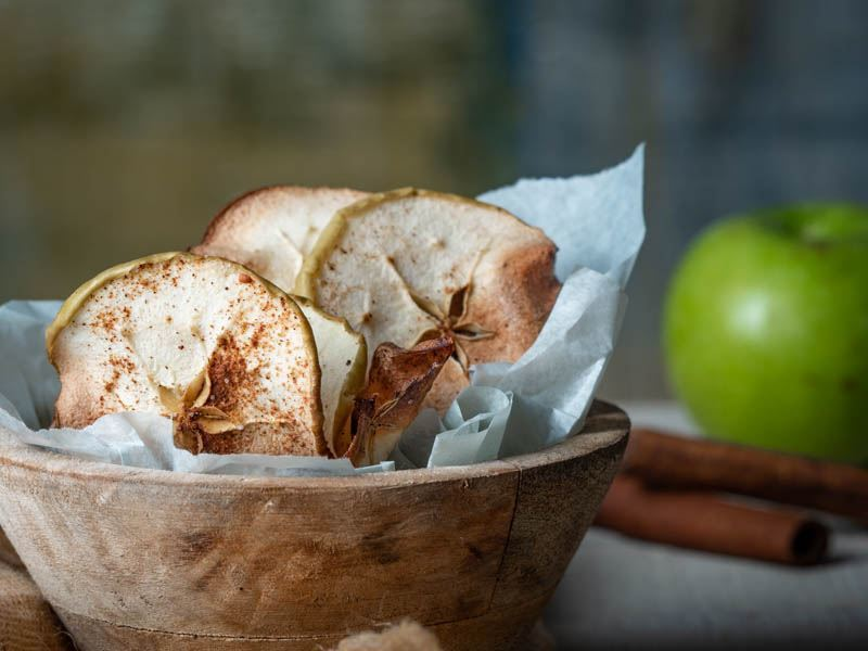 Cinnamon Apple Chips in a wooden bowl with apples and cinnamon sticks in the background. inthekitch.net
