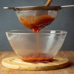 How to Make Ketchup - Step 5 straining ketchup into bowl - inthekitch.net