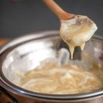 How to Make White Chocolate Ganache - Step 3 image of melted chocolate dripping from wooden spoon - inthekitch.net