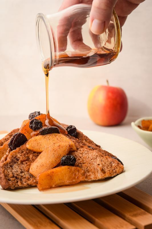 French Toast with Cinnamon Apple Garnish on a plate, on wood rack with maple syrup being poured over top.
