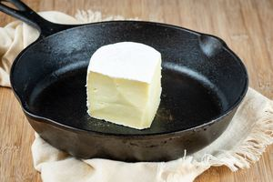 Brie wedge in a cast iron pan.