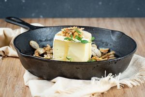 Brie in a cast iron pan with mushrooms oregano walnuts and honey.