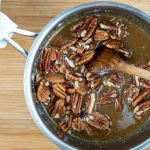 Mixing pralines into pot with sugar mixture.