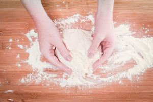 Hands mixing dough on floured surface.