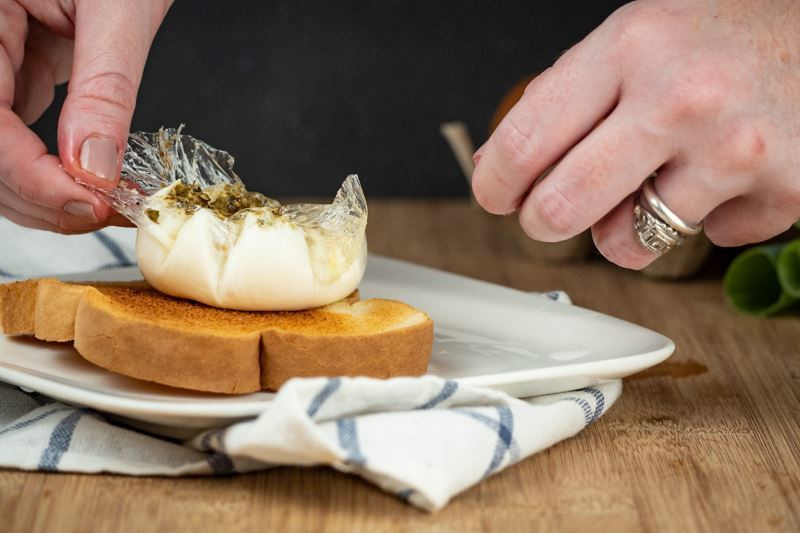 How to Sous Vide Eggs Step 10 Poached - opening egg pouch over toast.