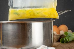 How to Sous Vide Eggs Step 3 Scrambled - placing scrambled egg plastic bag into pot.
