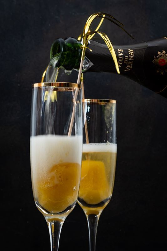 Pouring champagne into glasses with frozen peaches on the bottom.