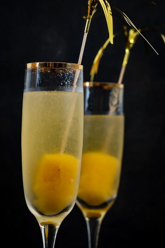 2 champagne glasses with champagne and frozen peach pops on bottom.
