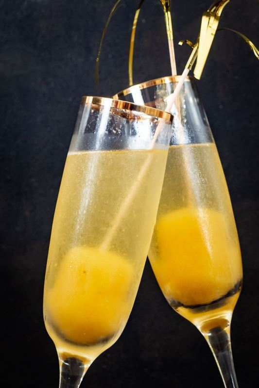 2 champagne glasses clinking together with champagne and frozen peach pops on bottom.