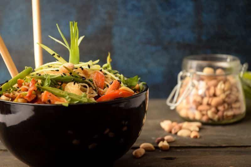 Vegan Pad Thai in a black bowl, peanuts in a jar in the background.