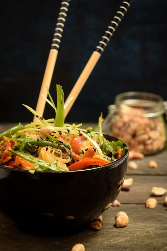 Vegan Pad Thai in a black bowl with chopsticks, peanuts in a jar in the background.