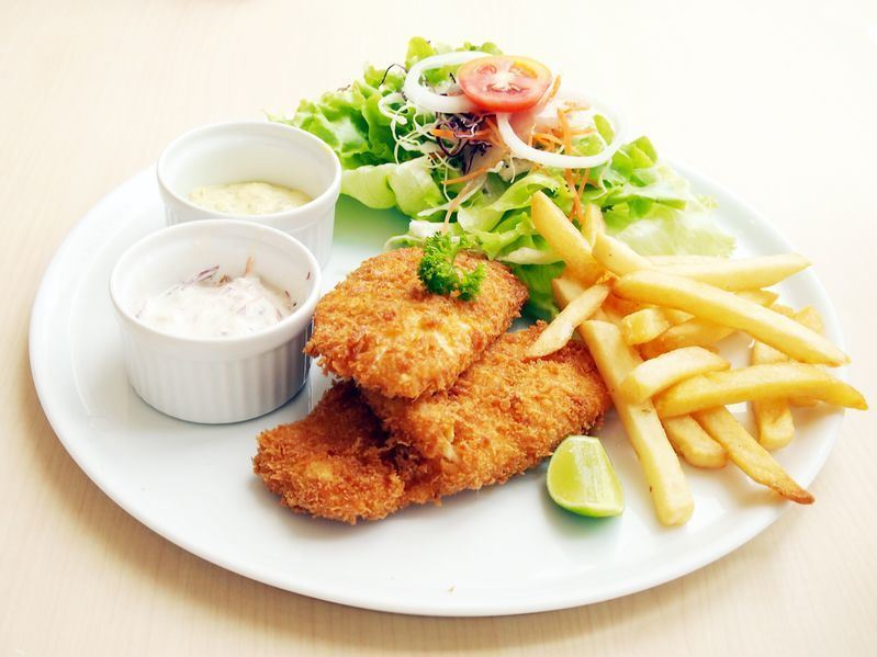 Crispy Fried Fish on a plate with fries, salad, lime wedge and dip.