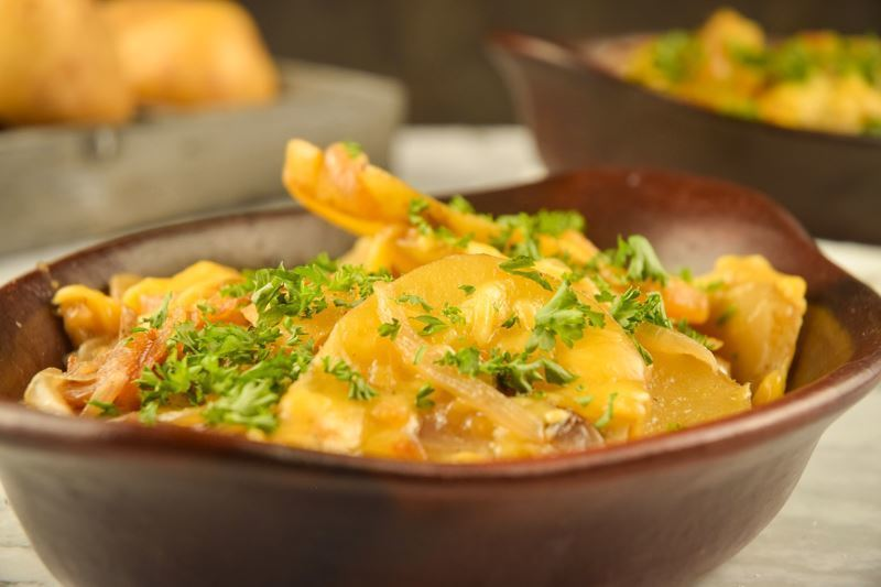 Electric Skillet Scalloped Potatoes in a wooden dish.