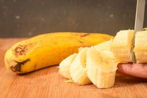 Slicing bananas on a cutting board.