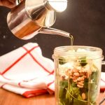 Pouring oil into magic bullet jar filled with pine nuts, feta, basic and arugula.