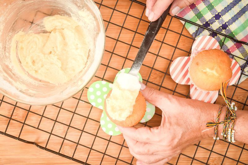 Using a spatula to frost cupcakes.