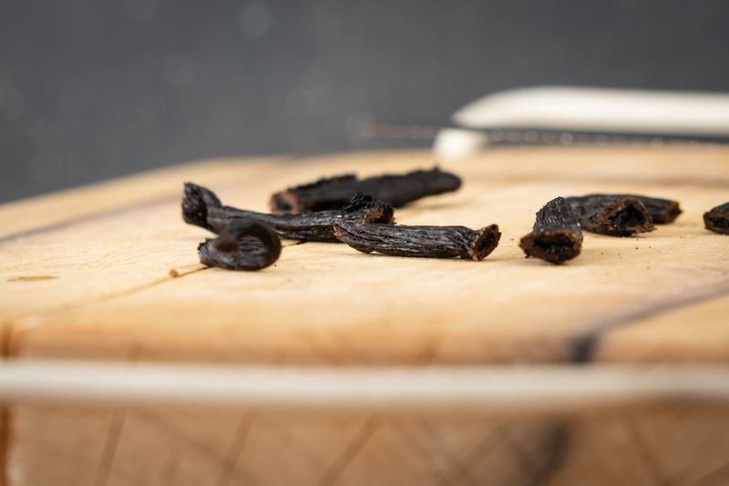 Chopped vanilla bean pods on a cutting board.