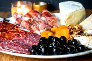 Finished Charcuterie Board with meat, cheese, olives and apricots.