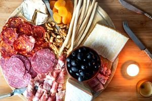 Finished Charcuterie Board with meat, cheese, olives, bread sticks and apricots.