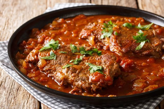 Skillet Swiss Steak on black plate, wood background.