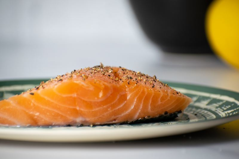Seasoned salmon fillet on plate.