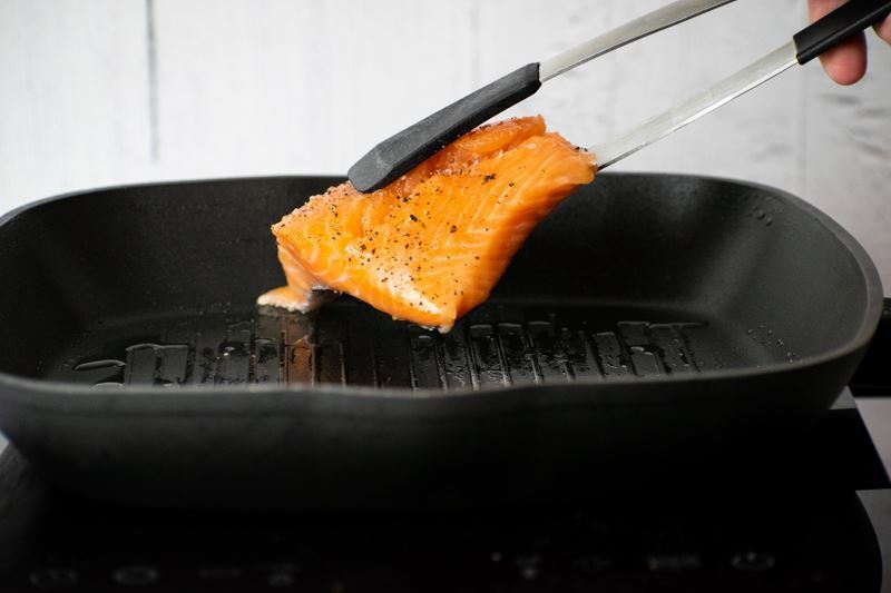 Adding raw salmon to pan, skin side down.