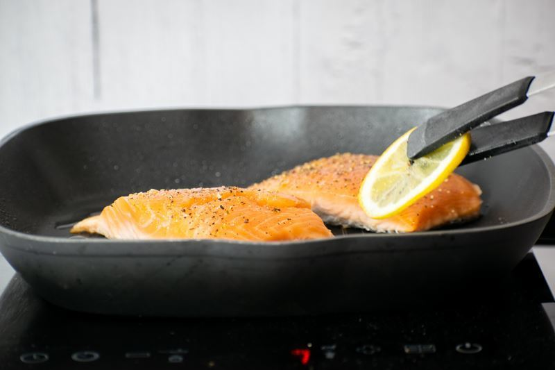 Adding a lemon slice to pan.