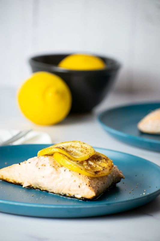 Cooked salmon with grilled lemon slice on plate.