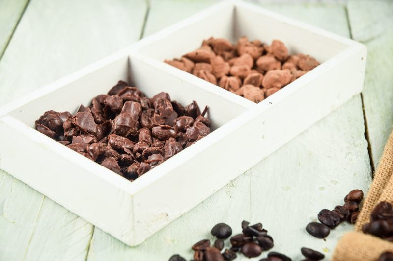 Chocolate and cocoa covered coffee beans in serving tray, coffee beans layed out on wooden background.