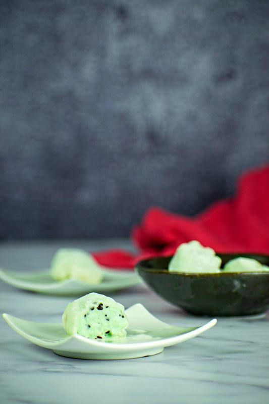 Mint green mochi ice cream that has been cut open, on a mint-colored dish.