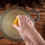 Hands squeezing lemon juice into pot of milk.