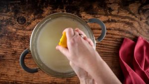 Hands squeezing lemon juice into pot of milk.