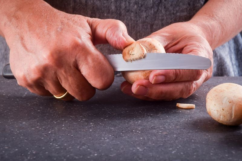 Slicing mushrooms with a serrated knife.