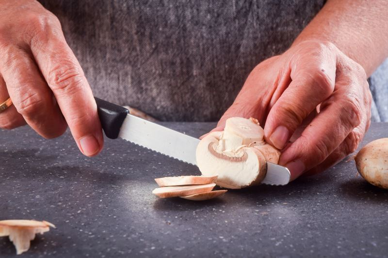 Woman slicing mushrooms with a serrated knife.