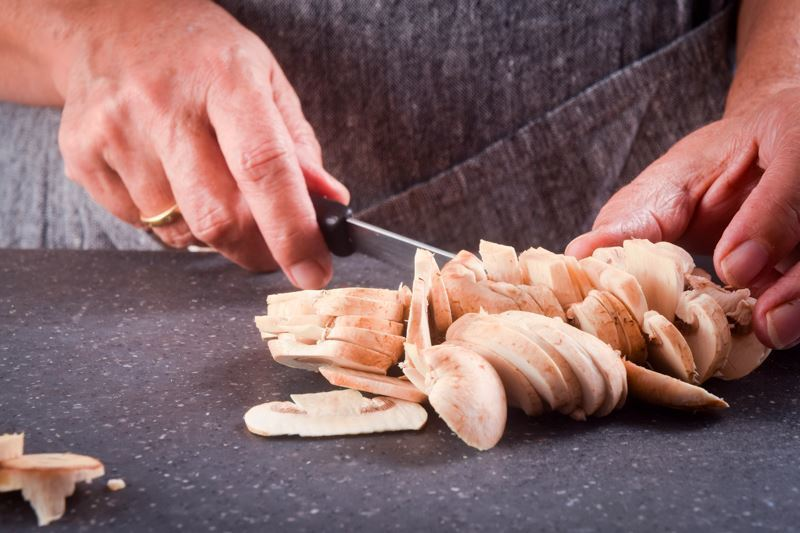 Sliced mushrooms on granite counter, chef holding a knife.