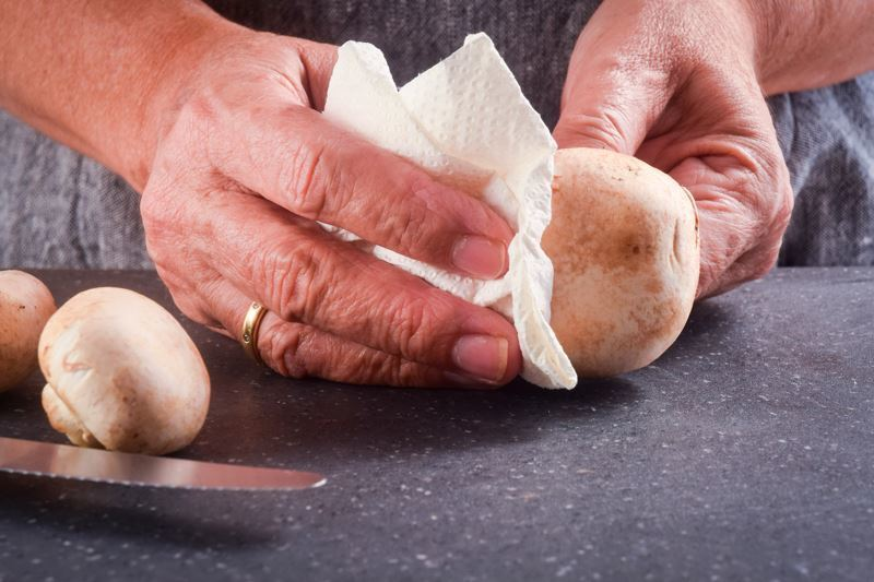 Hands cleaning mushrooms with a paper towel.