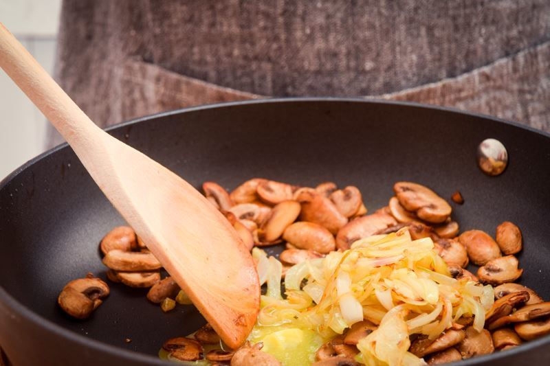 Using a wooden spoon to mix mushrooms and onions in pan.